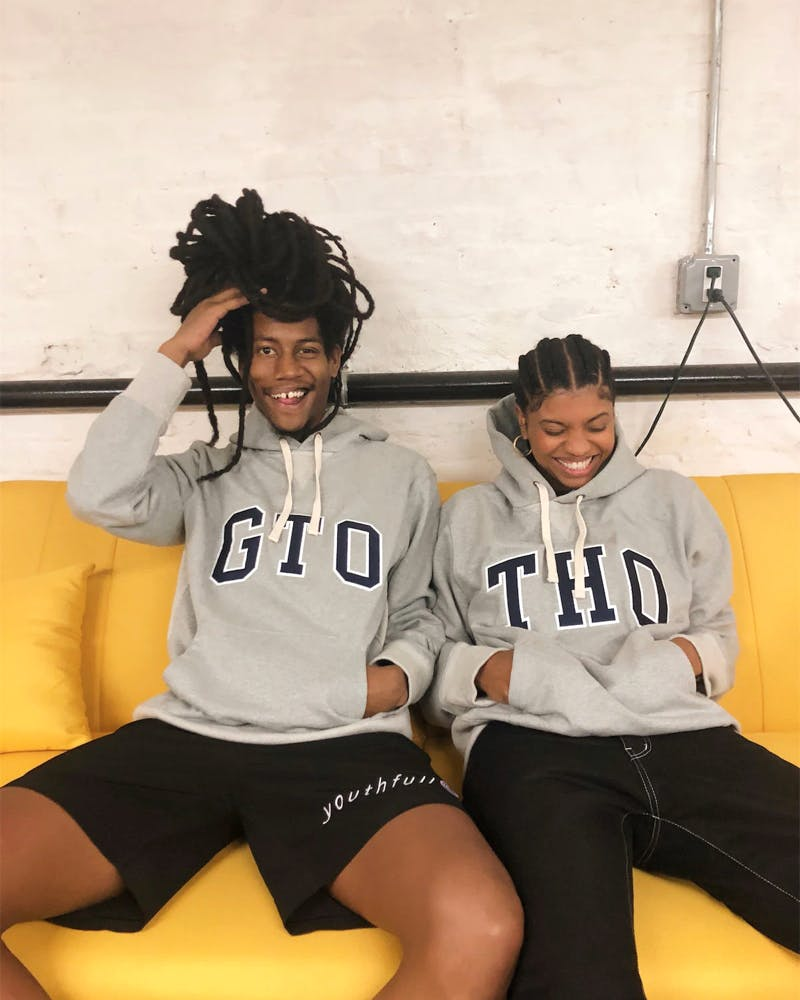 Two smiling people sitting on a couch wearing gap sweaters.