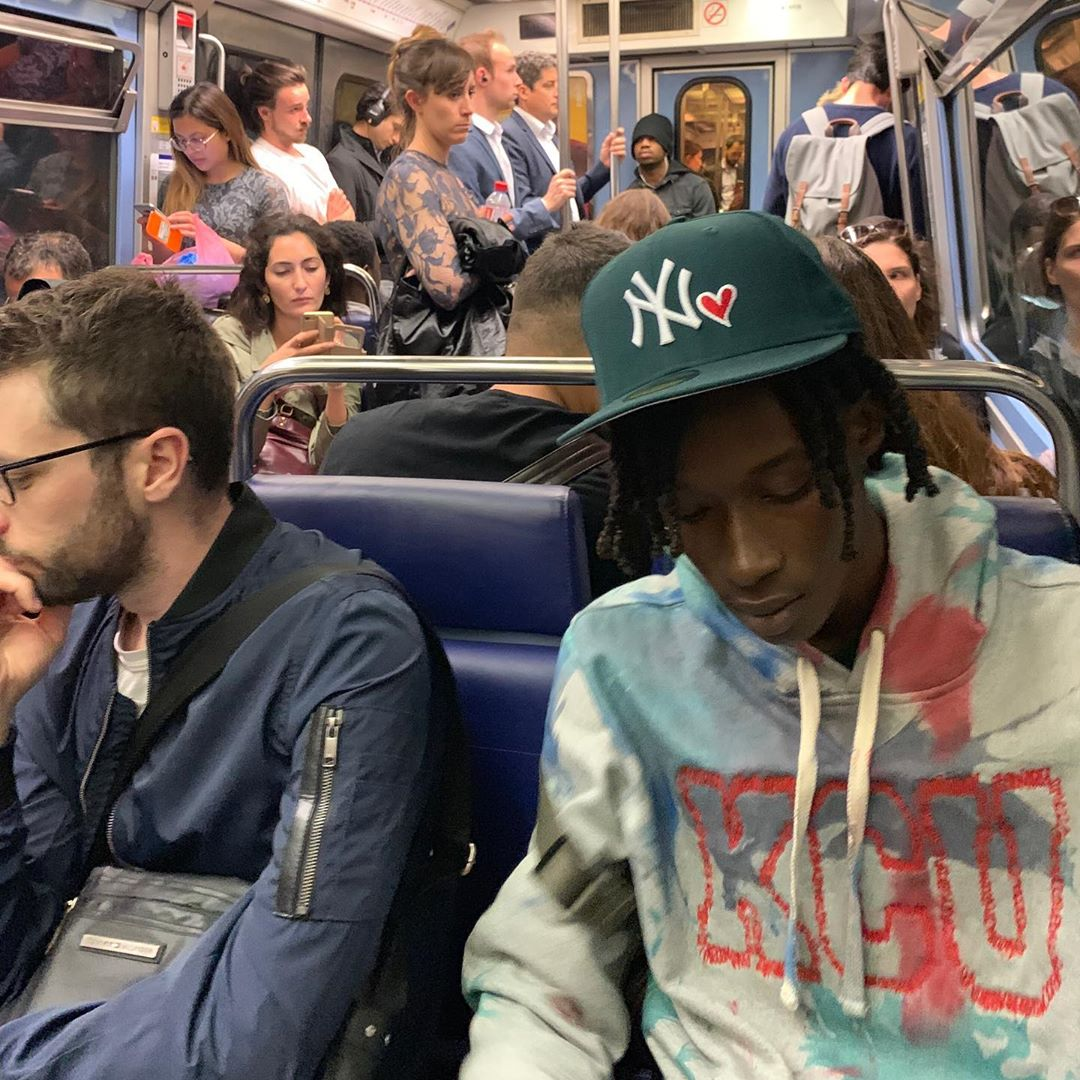 A man sitting in the subway wearing a gap sweater.
