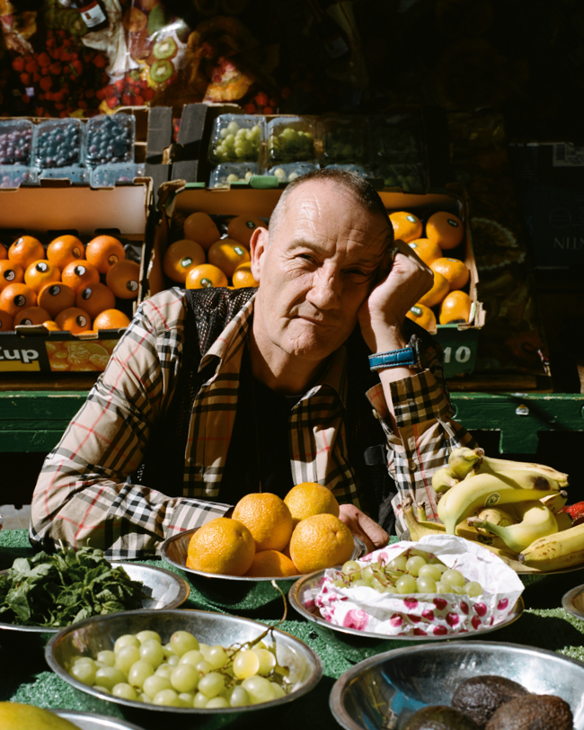 A man sitting between various bowls of fruit.