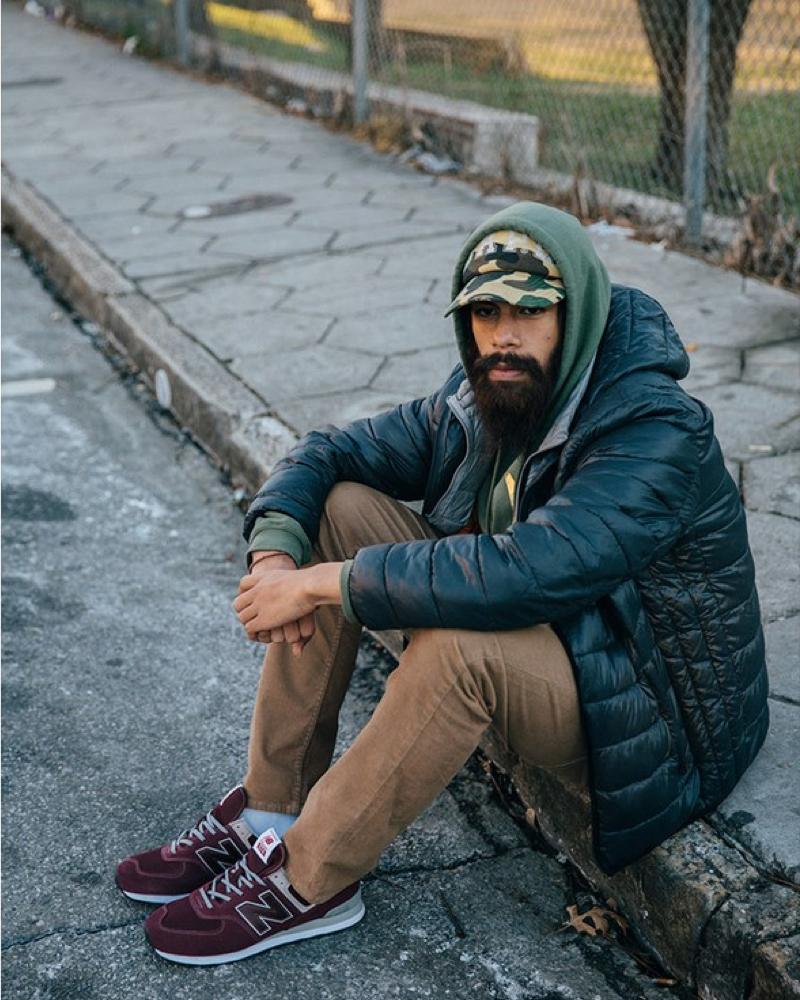 A man sitting on the sidewalk wearing new balance sneakers.