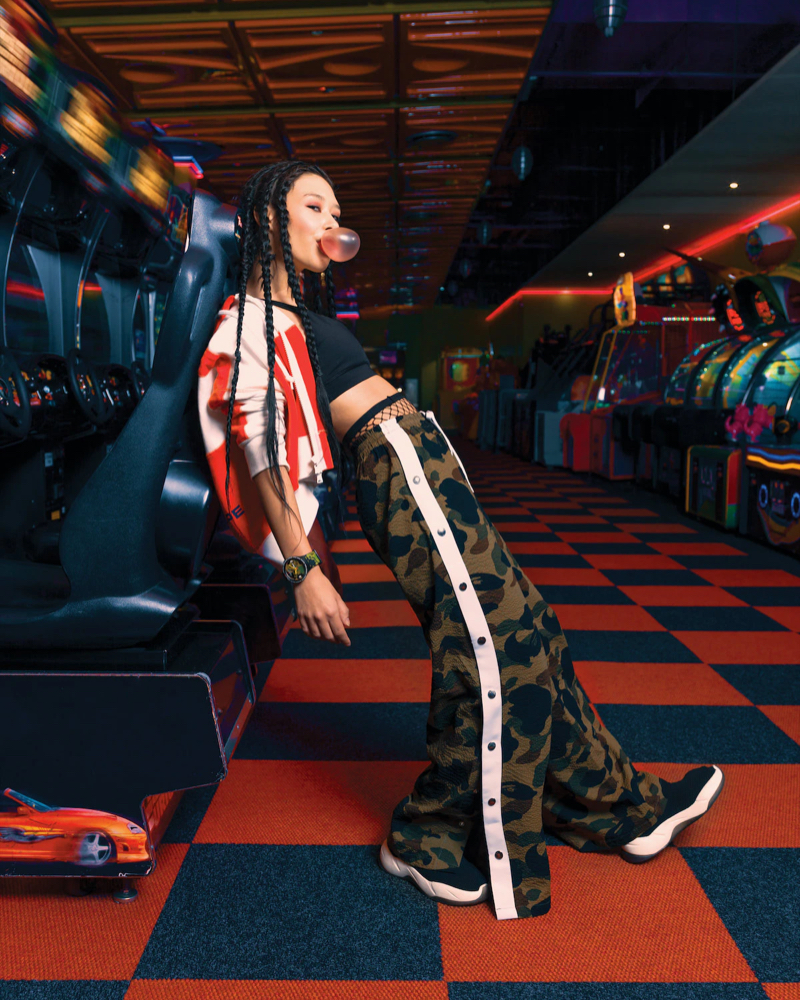 A woman posing in a arcade hall wearing a swatch x bape watch.