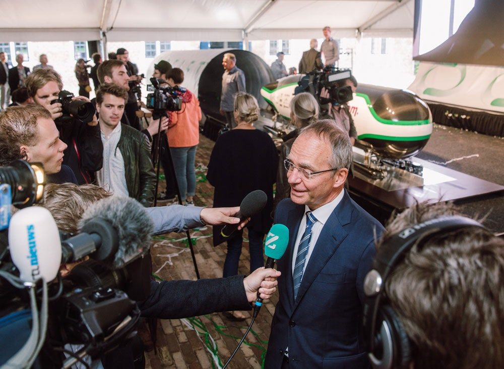 Minister Kamp is being interviewed during the press presentation of the Delft Hyperloop. The 'pod' is in the background.