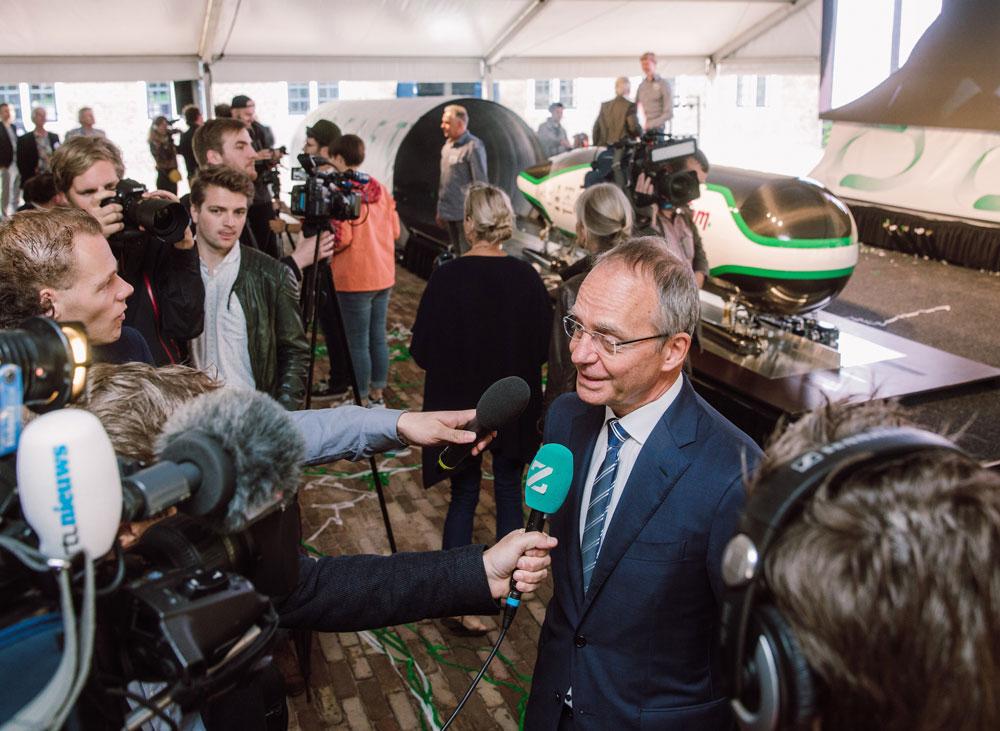 Minister Kamp wordt geïnterviewd tijdens de perspresentatie van de Delft Hyperloop. Op de achtergrond de 'pod'.