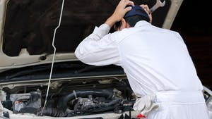 Side view of frustrated stressed young mechanic man in white uniform touching his head with hands against car in open hood at the repair garage.