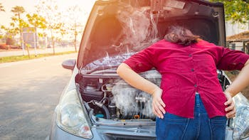 Woman dealing with an overheating car