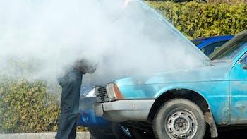 Man looking at a smoking engine