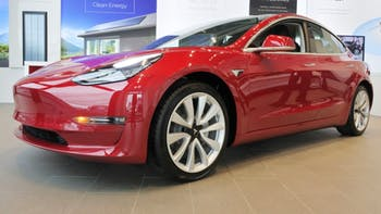 Red Tesla Model 3 inside the car shop