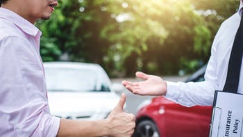 Insurance agent and customer shaking hands after the claim of contract