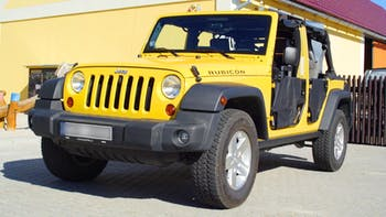 Yellow Jeep Wrangler parked in an open space
