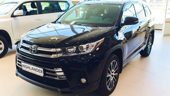 Black Toyota Highlander in Toyota showroom.