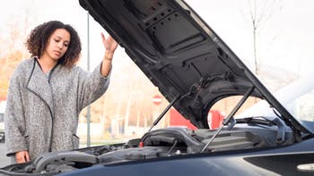Woman looking at broken down car's engine