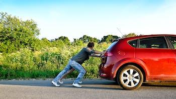 Man pushing broken down car