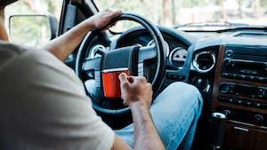 man driving with mug of tea