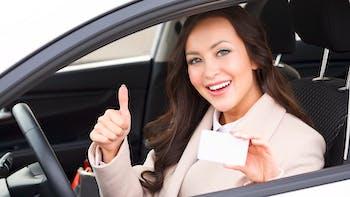 Girl sitting inside the car holding her license