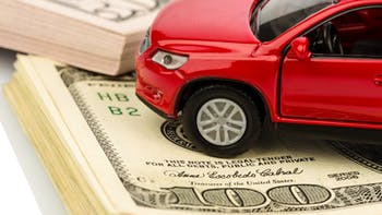 red model car on stack of hundred dollar bills