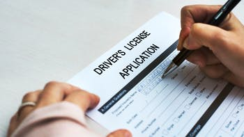 Person filling up the driver's license application form