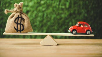 Red model car balanced with money