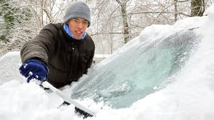 Man clears snow off car windshield
