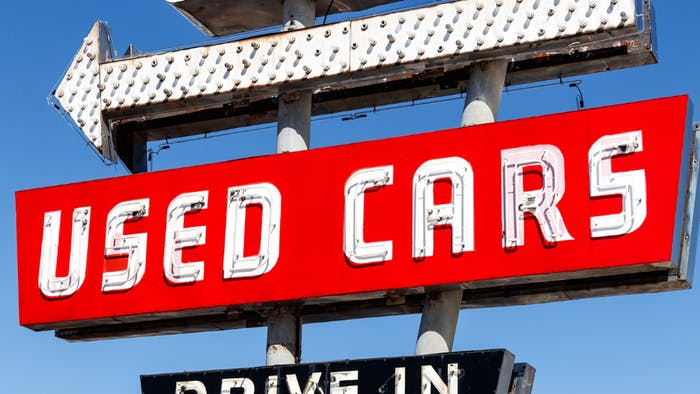 Old used car sign in red, with lights and neon