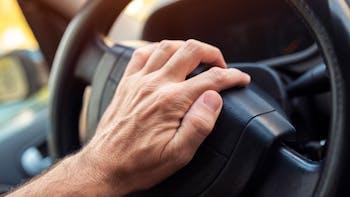 Hand on steering wheel honking horn