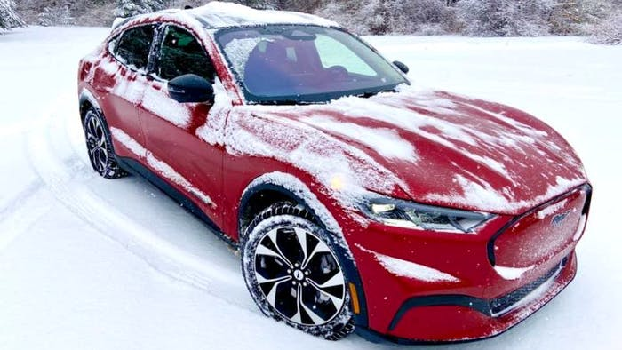 Red Ford Mustang covered in snow