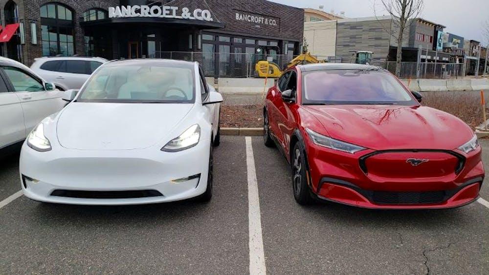 Beyaz Tesla Model Y'nin yanında Kırmızı Mustang Mach-E