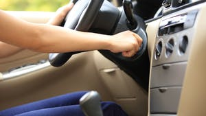 woman with hand on ignition starting manual transmission car