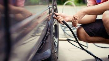 Man checking tire air pressure