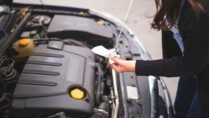A lady checking the car engine