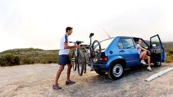 Man hanging a bicycle behind his car