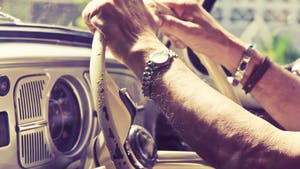 Close up of and old man's hand on the driving wheel