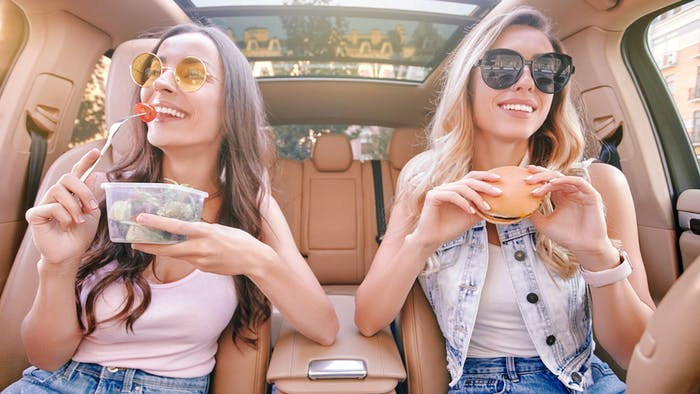 Two ladies with food sitting in the car