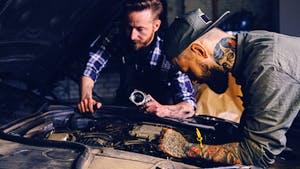 Two man checking a car engine