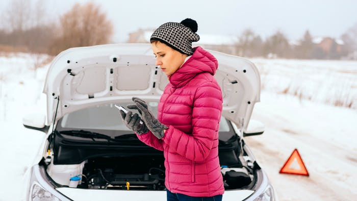 Woman in the middle of a snowy road with a broken car
