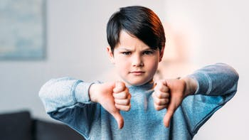 Boy showing thumbs down