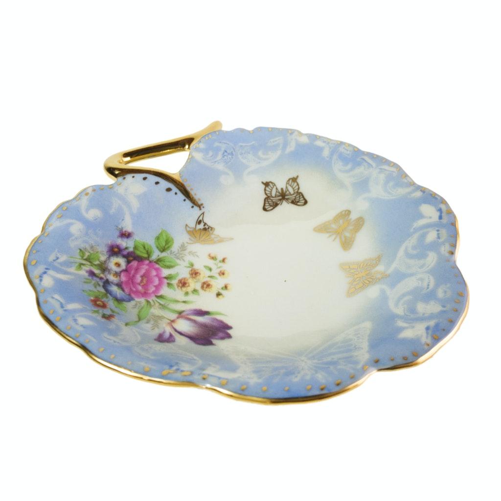 Peça de porcelana em formato de flor pintada em azul e dourado