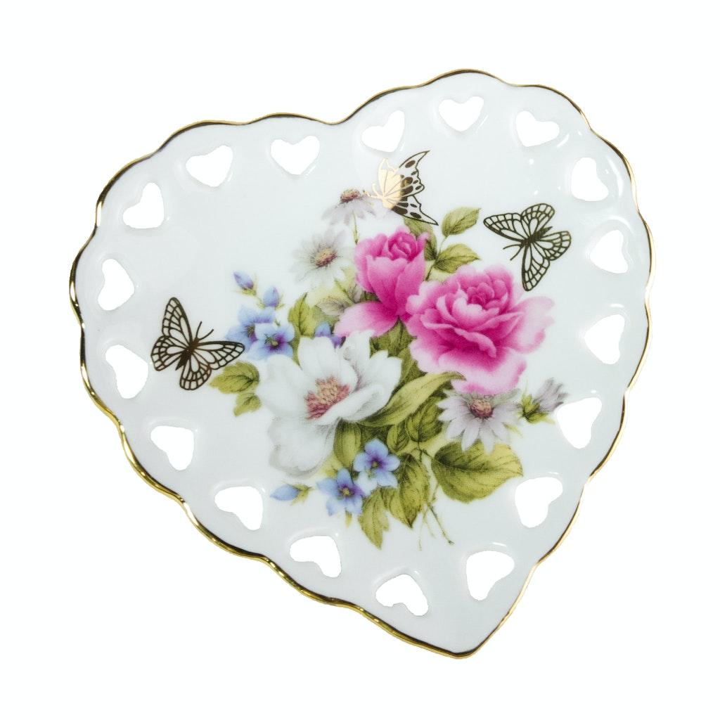 Peça de porcelana em formato de coração com flores e borboletas.