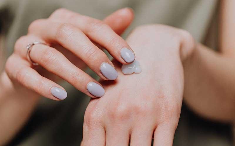 woman applying cream on her hand