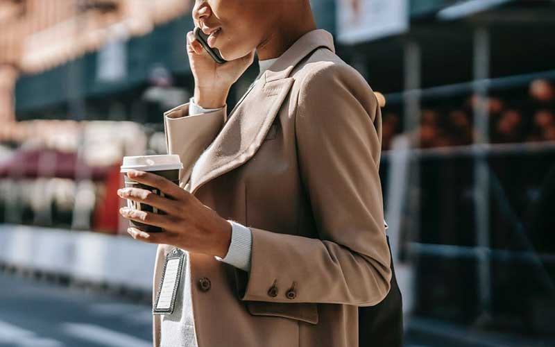 woman on the phone while holding a cup of takeout coffee