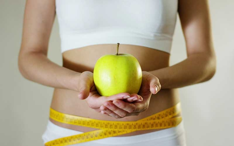 woman holding a green apple with a measuring tape around her waist
