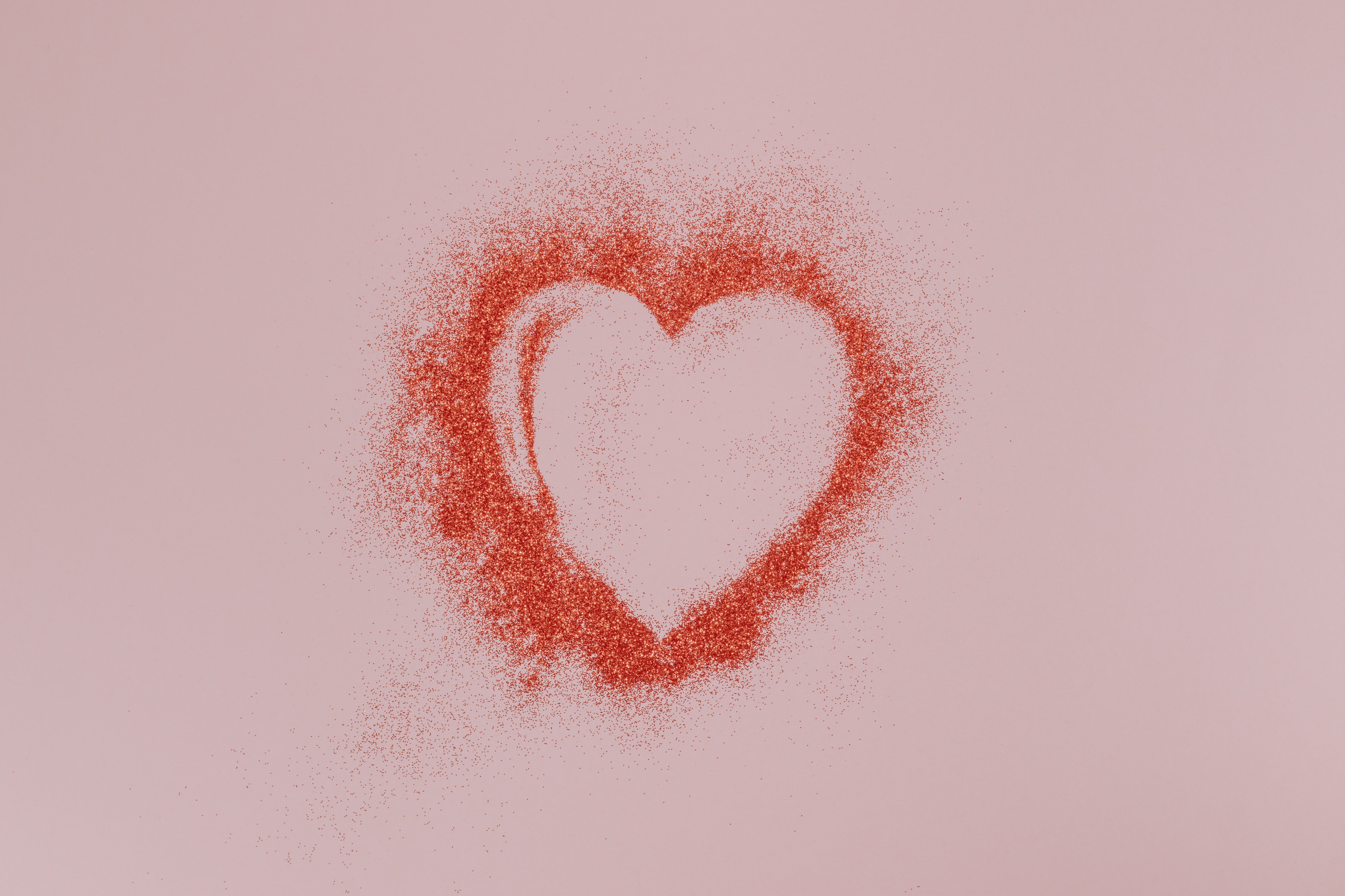 Love heart in red glitter on a pink background