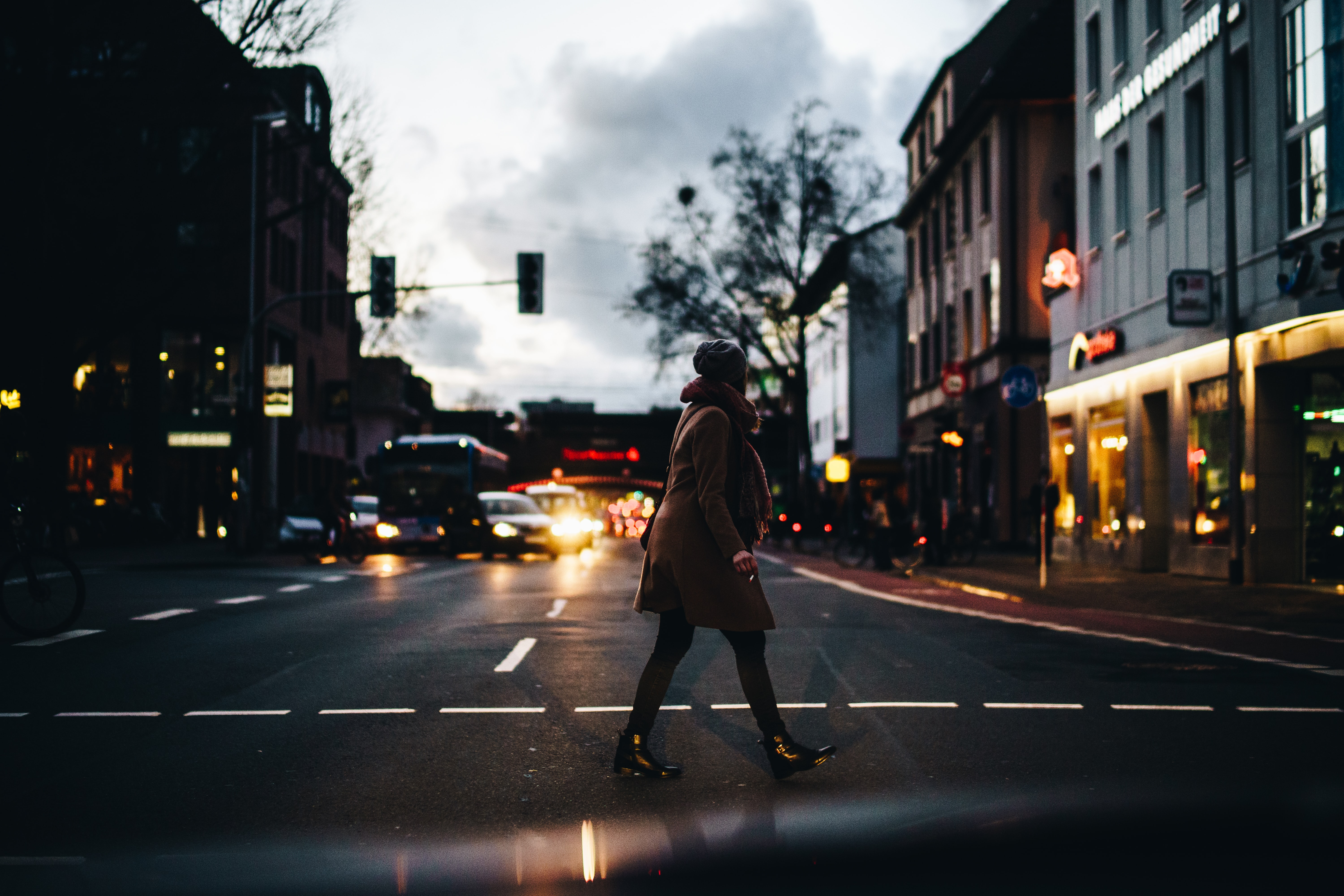 Woman walking on street with cars