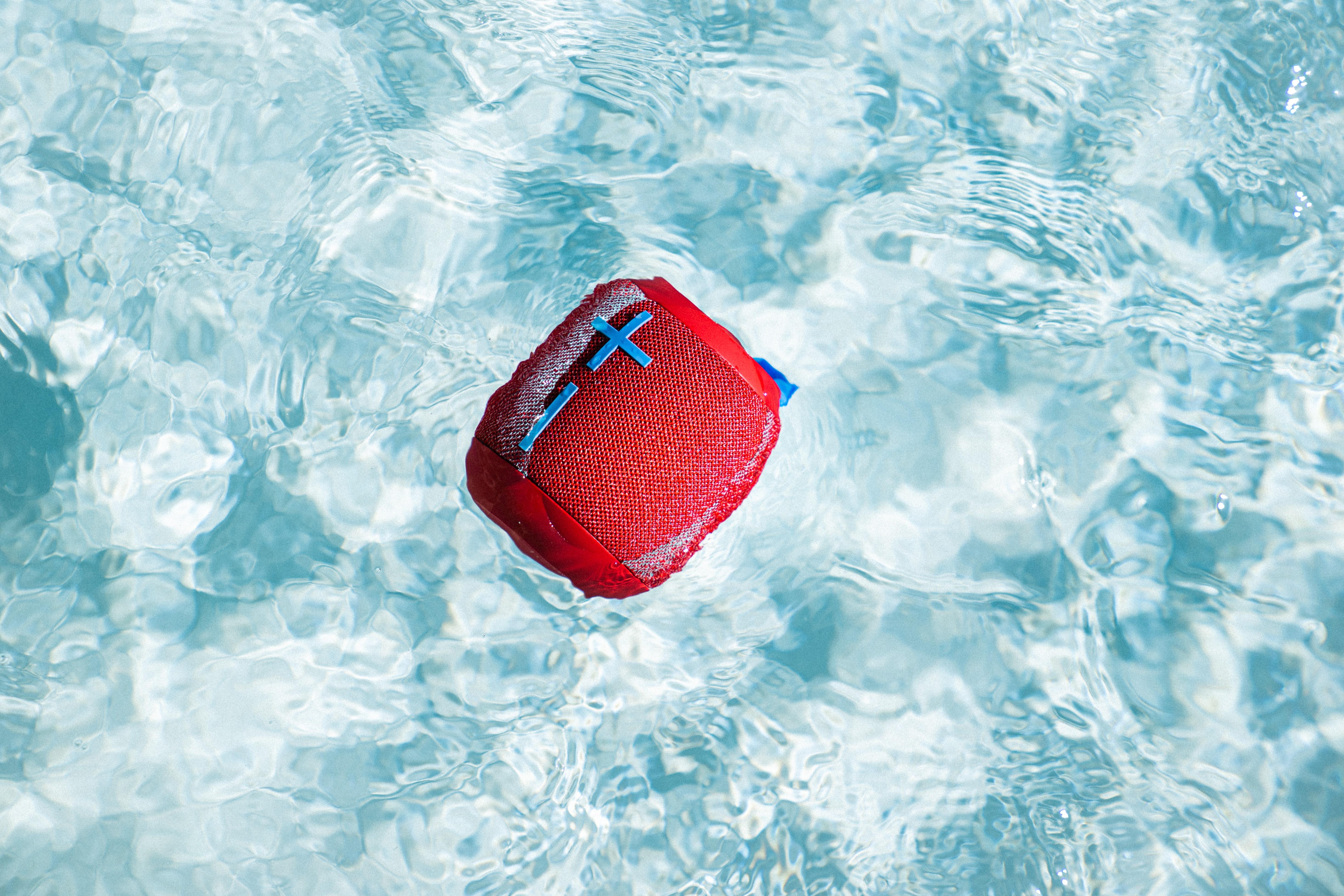 Red bluetooth speaker in pool
