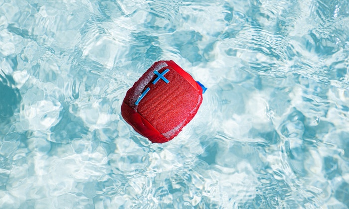 Red bluetooth speaker in pool