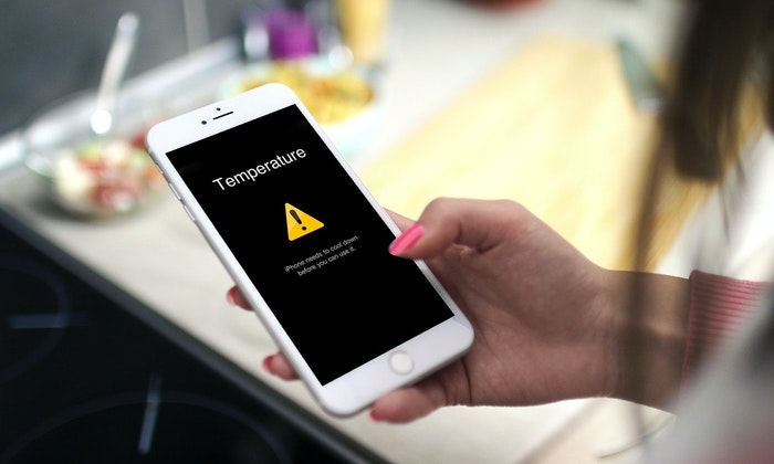 iphone with overheating message warning in the hands of a women