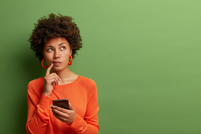 Woman thinks deeply about something and uses modern mobile phone