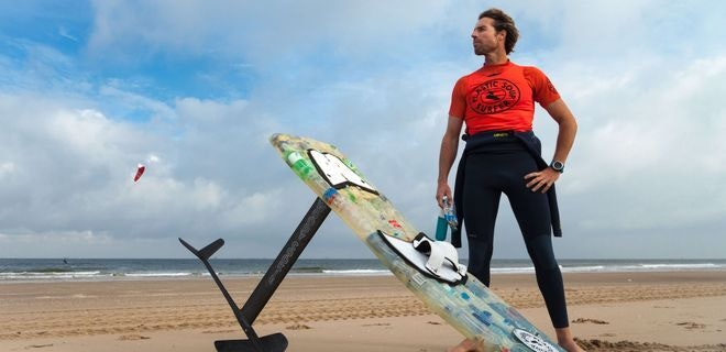 Foto van een man op het strand met een surfplank op de grond