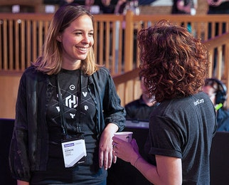 2 employees talking and laughing together at HashiConf 2017.