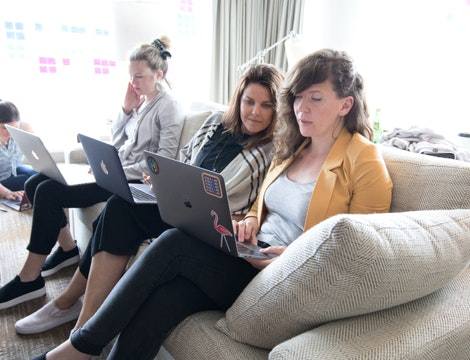 Four HashiCorp staff sitting on a couch working on laptops