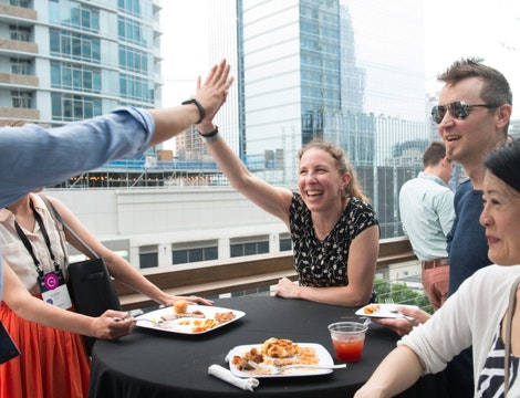 A collection of staff around a table with an urban backdrop. Two staff are high fiving each other